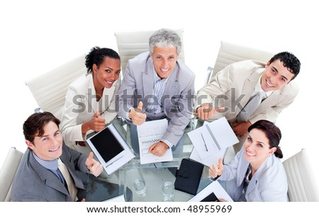 Smiling international business people with thumbs up in a meeting - stock photo