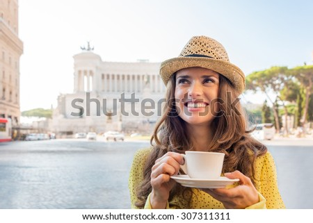 Smiling into the distance, a happy woman tourist enjoys a cup of Italian coffee with the Venice Square monument in the background. - stock photo
