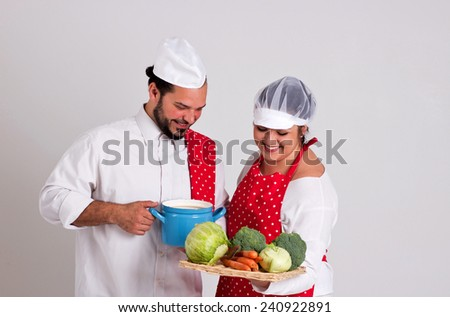 Smiling Italian Chief cook and Handsome Dark Hair Coo ky are Preparing Vegetable Soup Isolated on White Background - stock photo
