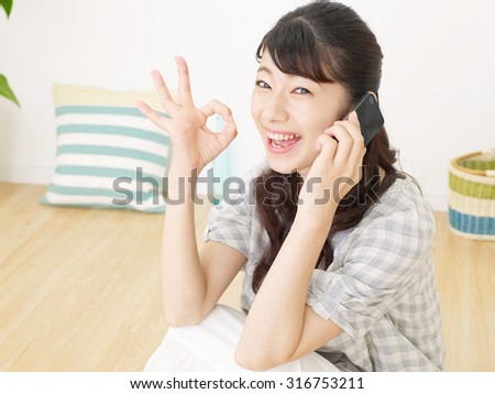 smiling Japanese woman OK gesture with the smart phone - stock photo