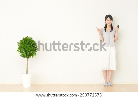 smiling Japanese woman point with the smart phone - stock photo