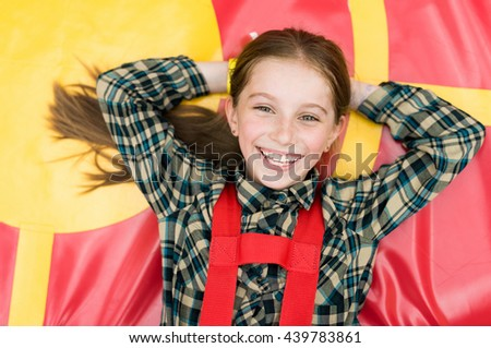 smiling joyful girl lying on colorful trampoline in entertainment center - stock photo