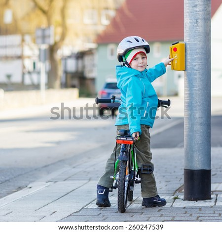 Smiling kid boy of 5 years riding with his first green bike in the city. Happy child in colorful clothes standing near traffic lights. Active leisure for kids outdoors.