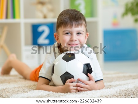 smiling kid boy with foot ball  indoor - stock photo