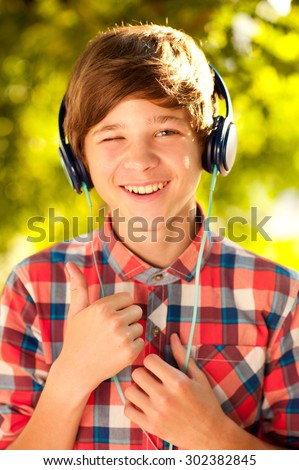 Smiling kid boy 14-16 year old listening to music outdoors. Childhood. Enjoyment.