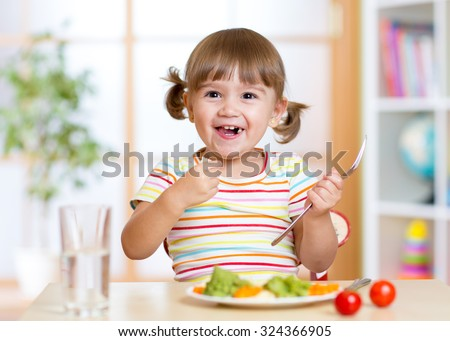 smiling kid girl eating healthy vegetables at kitchen - stock photo