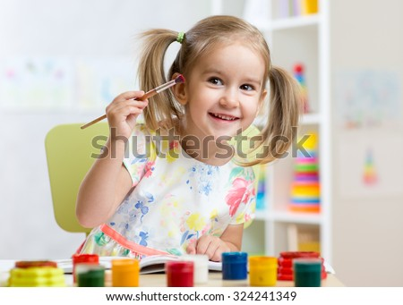 smiling kid girl painting at home or kindergarten