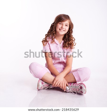 Smiling kid girl sitting on floor. Wearing sport clothes. Fitness exercise. Isolated over white