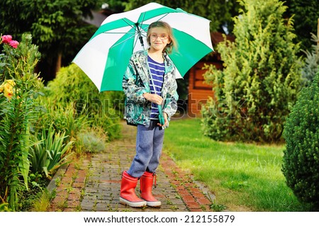 Smiling  kid girl with umbrella in raincoat and boots outdoor - stock photo