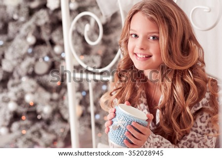 Smiling kid girl 10-12 year old holding tea cup sitting in bed over Christmas tree in room. Looking at camera. Celebration. Holiday time. - stock photo