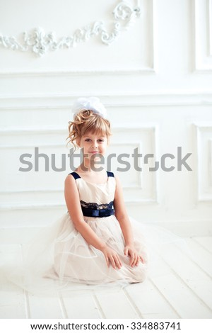 Smiling kid girl 4-5 year old wearing birthday style dress in room. Sitting on wooden floor. Looking at camera. Childhood.
