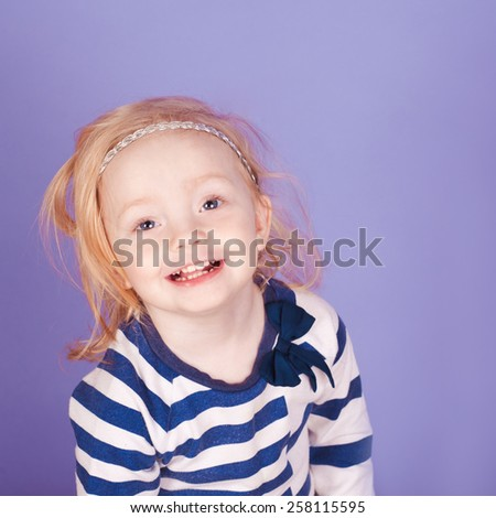 Smiling kid girl 2-3 year old wearing striped marine style shirt. Looking at camera. Childhood. - stock photo