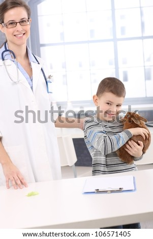 Smiling kid holding pet rabbit at veterinary office. - stock photo
