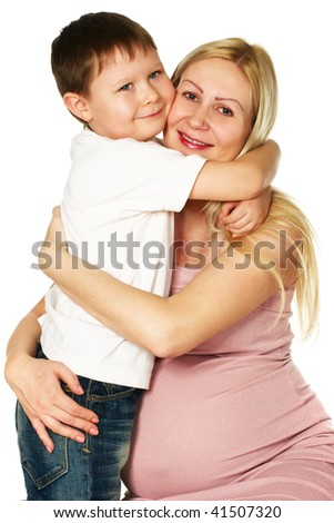 smiling kid hugging his pregnant mother - stock photo