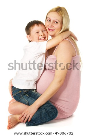 smiling kid hugging his pregnant mother