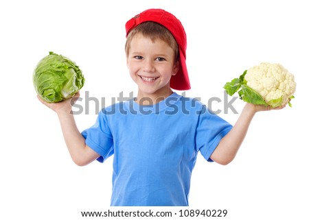 Smiling kid in red hat with cabbage and cauliflower, isolated on white - stock photo