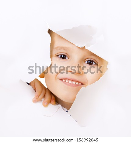 Smiling kid looking out of a hole of white paper
