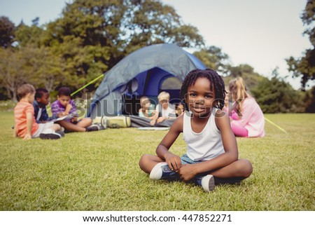 Smiling kid posing on grass during a sunny day with other children at park - stock photo
