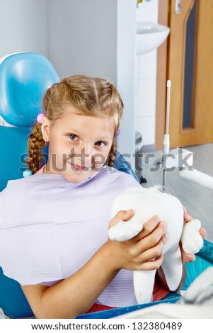 Smiling kid sitting in chair with a toy tooth - stock photo