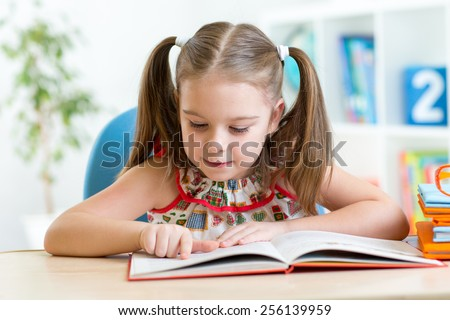 smiling kid student girl reading book in children room - stock photo