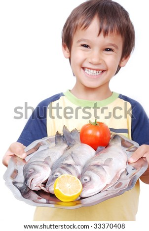 Smiling kid with three fresh fishes on table - stock photo