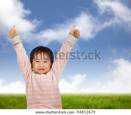 Smiling kid with thumbs up and standing on the green meadow - stock photo