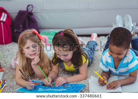 Smiling kids drawing pictures on paper on the floor
