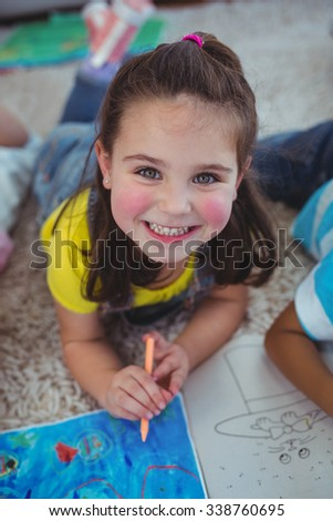 Smiling kids drawing pictures on paper on the floor - stock photo