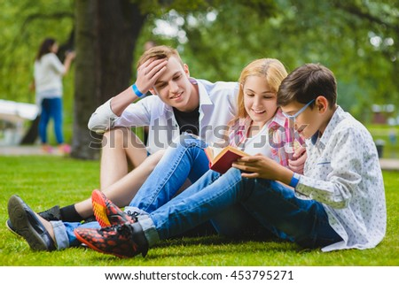 Smiling kids having fun and reading book at grass. Children playing outdoors in summer. teenagers communicate outdoor - stock photo
