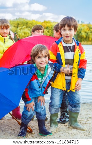 Smiling kids having fun with autumn umbrellas in the outside - stock photo