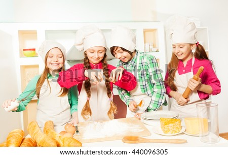 Smiling kids in cook's uniform making bakery dough - stock photo