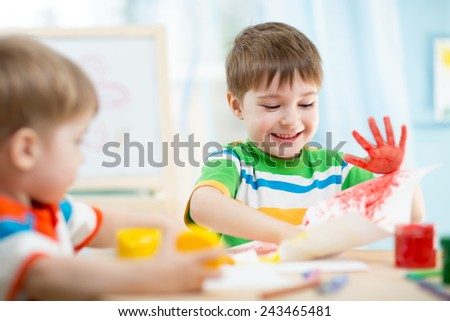 smiling kids playing and painting at home or kindergarten or playschool - stock photo