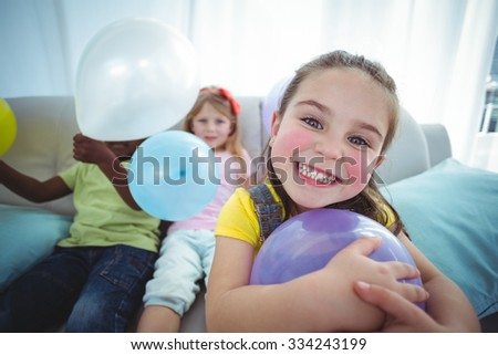 Smiling kids playing with balloons on the couch