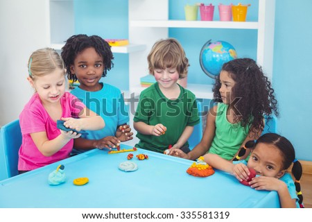 Smiling kids playing with modelling clay at their desk - stock photo