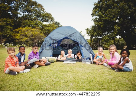 Smiling kids posing in the tent together during a sunny day at park - stock photo
