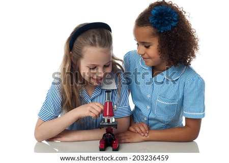 Smiling kids trying to learn use of microscope - stock photo