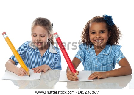Smiling kids writing their annual exam - stock photo