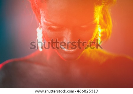 Smiling lady bends her head while red and green light illuminate it