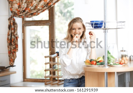 Smiling lady eating vegetables at kitchen - stock photo