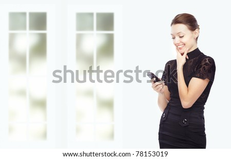 Smiling lady indoors taking pleasure from the cell phone - stock photo