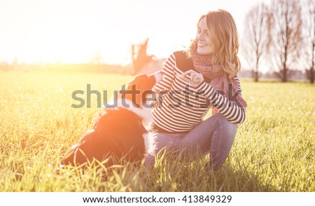 Smiling lady taking free time with her dog.Woman  relaxing in the nature with her loyal dog - stock photo