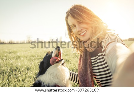 Smiling lady taking selfie with her dog. Woman and her loyal border collie dog - stock photo