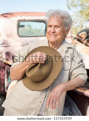 Smiling lady with a hat leaning against a vintage truck - stock photo