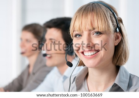 Smiling lady working at call center office with colleagues - stock photo