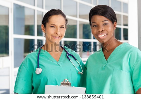 Smiling latin and afro-american nurse holding a clipboard in brightly lit exterior hospital environment in scrubs, white lab coat and holding glasses. - stock photo