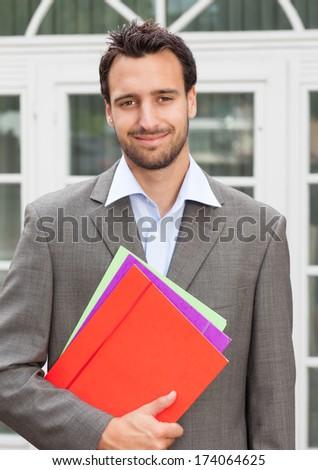Smiling latin businessman with paperwork   - stock photo