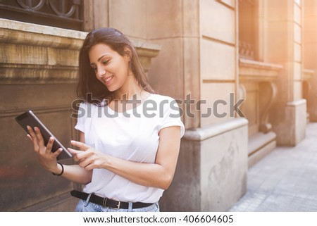 Smiling latin woman is watching photo that she just take on digital tablet camera while is walking on the street, happy female tourist is using touch pad for navigation during her summer vacation trip - stock photo