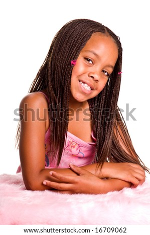 Smiling little African American girl with finger braids with her elbows on the bed - stock photo