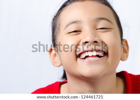 smiling little asian girl wearing red knitted sweatshirt on isolated white background