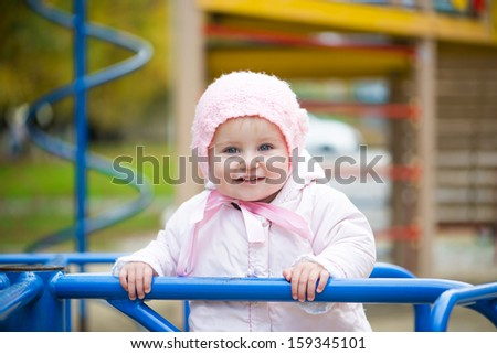 smiling little baby in a swing at the park - stock photo